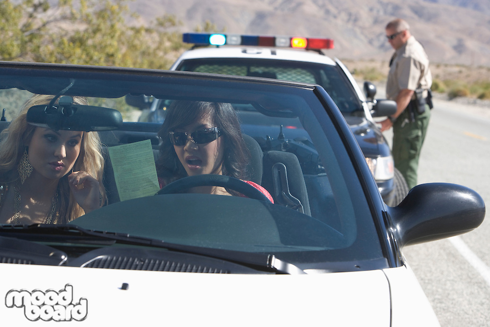 Two young women reading speeding ticket in car