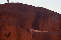 naked man on a red rock ledge in Utah