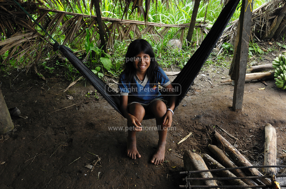 Ecuador, May 6 2010: A young Huaorani girl smiles for the camera while sitting in a hammock. Copyright 2010 Peter Horrell