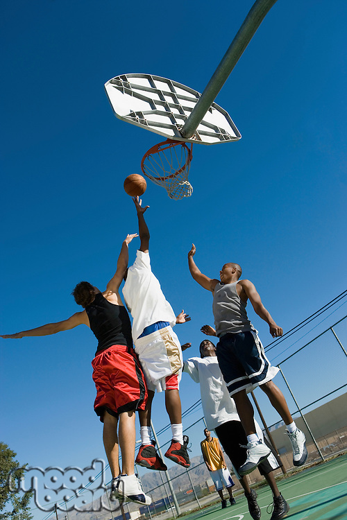 Two basketball players guarding another as he tries to shoot basketball low angle view