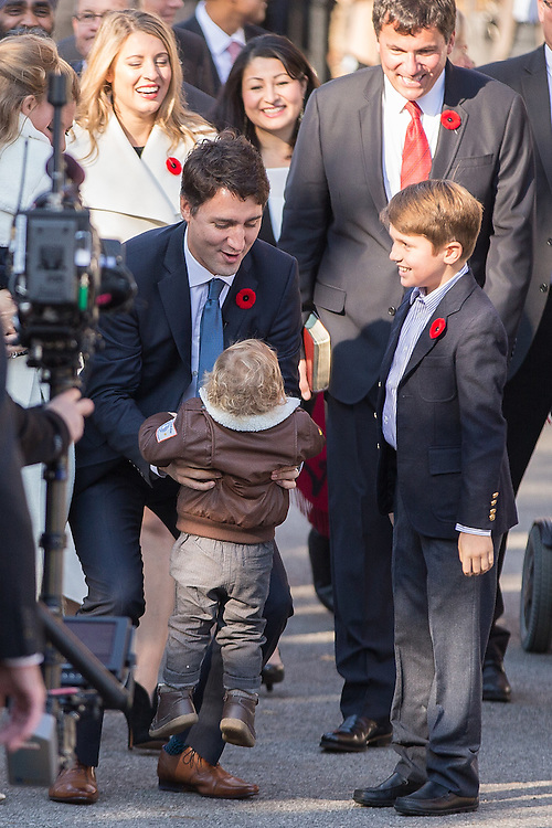 Prime Minister designate Justin Trudeau lifts his son Hadrian as he arrives at Rideau Hall to be sworn in as the 23rd Prime Minister in Ottawa, Ontario, November 4, 2015.<br /> AFP PHOTO/ GEOFF ROBINS