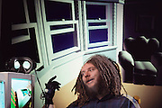 Virtual reality: Jaron Lanier, head of VPL Research of Redwood City, California, photographed surrounded by demonstration images of the virtual, non-real worlds that VPL have created. Fiber- optic sensors in the black rubber glove Lanier is wearing tranmsit a user's movements into the computer-generated virtual environment. A user's view of such a world is projected by the computer into 2 eyephones mounted on a headset (seen unworn at left, on top of the computer monitor). Model Released (1990)