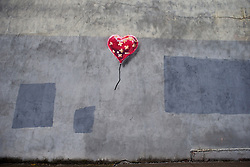 "Banksy graffiti art in New York City. <br /> People gather in front of a new Banksy piece of a bandaged heart shaped ballon which appeared today, 7th October, 2013 in the Red Hook section of Brooklyn, NY. Banksy is doing a residency on the streets of New York City, titled ""Better Out Than In"" for the month of October, Monday, 7th October 2013. Picture by Michael Graae / i-Images"