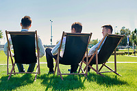 Group of handsome businessmen relaxing and talking about life while sitting on folding chair at park