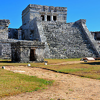 El Castillo Full View at Mayan Ruins in Tulum, Mexico<br /> Most of the Tulum&rsquo;s buildings are short, boxy and devoid of ornamentation except for the city&rsquo;s centerpiece: The Castillo.  It was the largest building in Zam&aacute; but much smaller than several Mayan pyramids on the Yucat&aacute;n Peninsula. Evidence suggests El Castillo was constructed in stages. The grand staircase leads to a platform at the temple entrance which is supported by upside-down serpent columns. At the corners are threatening masks borrowed from the Toltec culture.  In the center is a craving of the Descending God, the deity believed to have been worshiped in this ancient Mayan community.