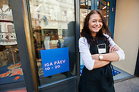 Portrait of smiling saleswoman standing arms crossed outside supermarket