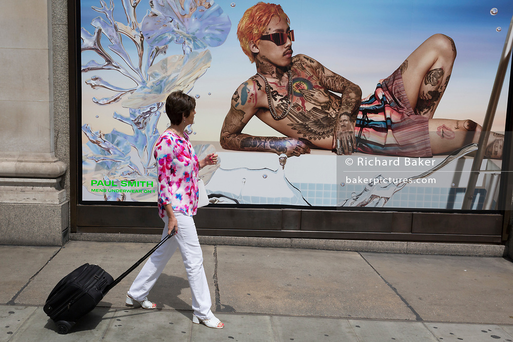 An middle-aged lady admires a sexy young male in an advert for mens' underwear outside the London location of the Selfridges Department store on Oxford Street, on 2nd July 2019, in London, England.