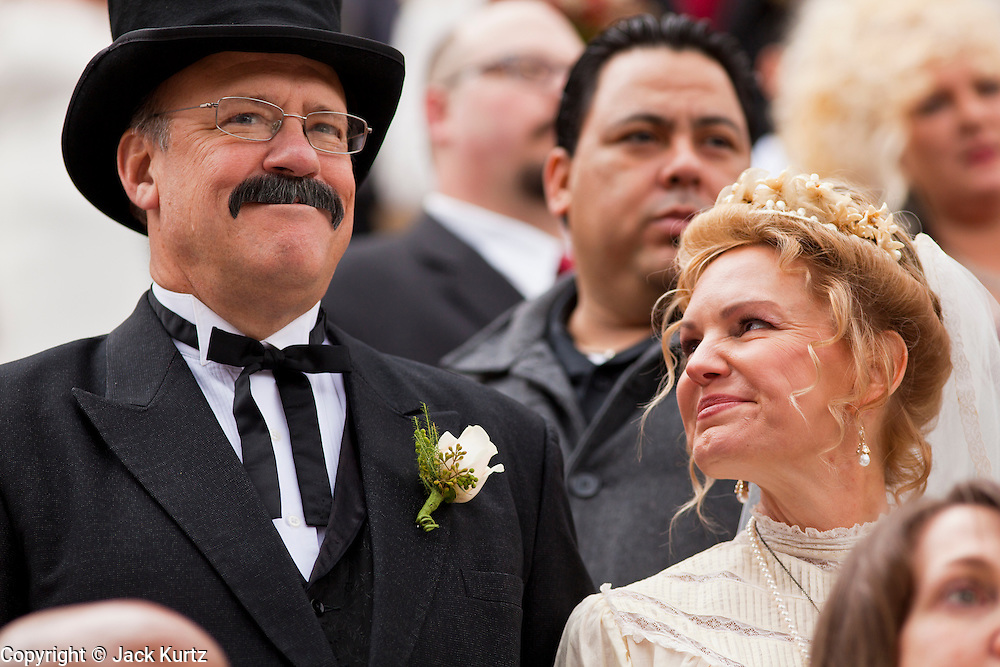 14 FEBRUARY 2012 - PHOENIX, AZ:    JIM OGSBURY and CHRISTINE COOK exchange wedding vows during a mass wedding ceremony in Phoenix Tuesday. Ninetysix couples got married in a mass ceremony on the steps of the Arizona Supreme Court to mark the Valentine's Day holiday. The wedding was also an occasion to mark Arizona's centennial of statehood.    PHOTO BY JACK KURTZ