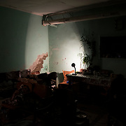 A desk lamp illuminates the decayed wall of a underground bomb shelter of a school outside Donetsk. During this period, several families were living here for several months to protect themselves from heavy exchange of shelling between pro-Russian separatist fighters and Ukrainian military forces.