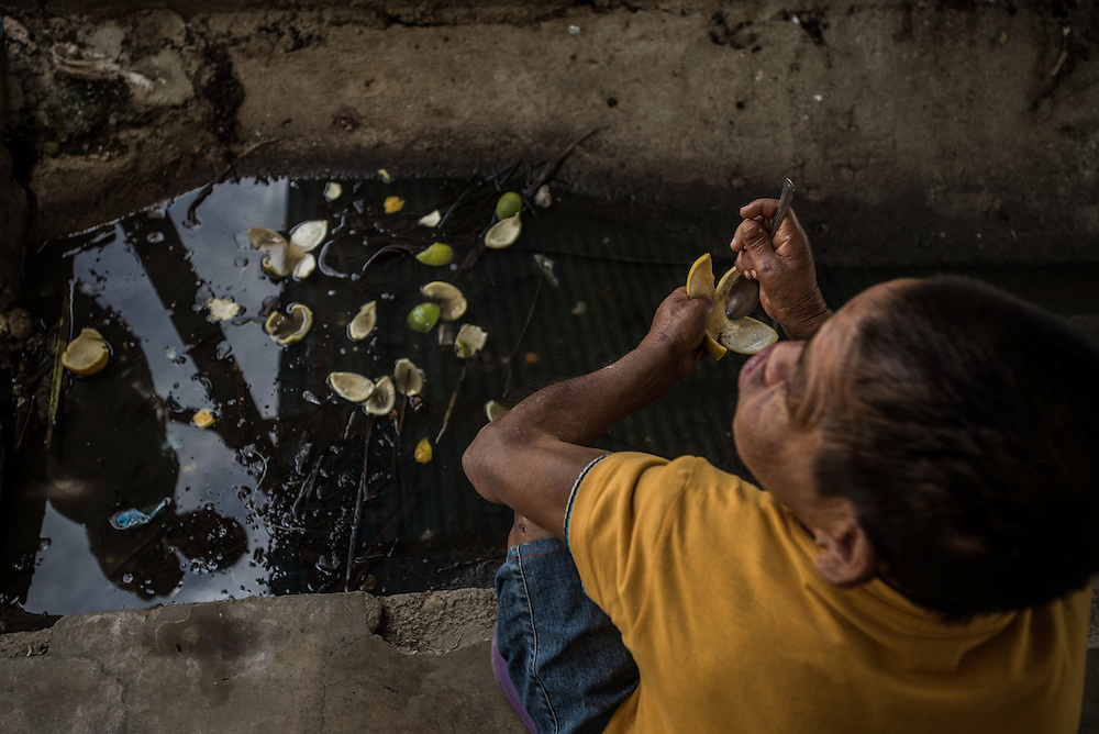 BARQUISIMETO, VENEZUELA - AUGUST 24, 2016: Alba Peralta, a patient diagnosed with epilepsy and mental retardation, and infected with scabies, eats discarded orange peels from contaminated black water full of feces, at a spot where patients relieve themselves in the open patio area of the women's ward. She became violent when other more stable patients tried to make her stop. She does not have any of the 5 drugs that doctors prescribed to her for her condition.  The economic crisis that has left Venezuela with little hard currency has also severely affected its public health system, crippling hospitals like El Pampero Psychiatric Hospital by leaving it without the resources it needs to take care of patients living there, the majority of whom have been abandoned by their families and rely completely on the state to meet their basic needs, and who could live much more fulfilling lives if they had the medicines that they need.  When a patient loses control, often the only thing they can do is lock them in an isolation cell to prevent them from hurting themselves, other patients and members of the staff. The hospital does not even have basic hygiene or cleaning supplies.  There is no soap, no shampoo, no tooth paste, no toilet paper.  Patients relieve themselves in the common areas and patio area, and clean themselves only with water. Nearly every patient is infected with scabies because they do not have the resources to bathe properly or to have their threadbare clothes washed regularly. PHOTO: Meridith Kohut