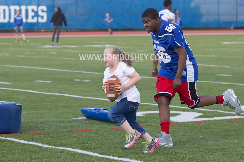 Middletown, New York - A young girl runs with the football as a Middletown High School football player chases her during a drill at Faller Stadium during Family Fun Night on May 17, 2013.