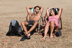 © Licensed to London News Pictures. 07/08/2018. London, UK.  Callum and Ria (from Eastbourne) sunbathe on dry grass in St James's Park in London during another day of hot and sunny weather in the capital.  Photo credit: Vickie Flores/LNP