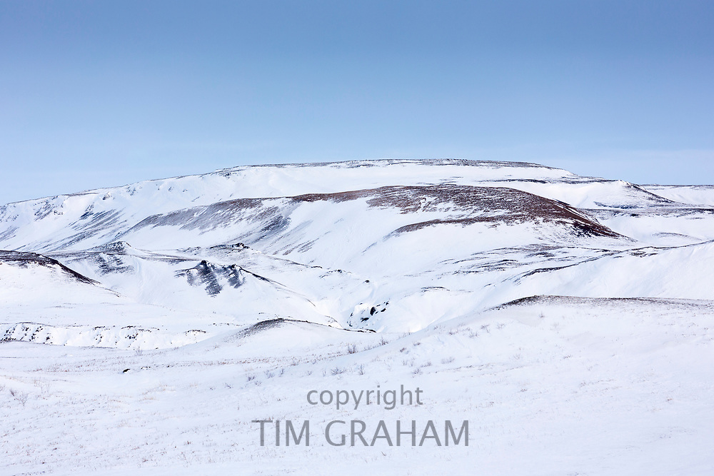 Typical Icelandic landscape scene of gently sloping contours and curves of snow covered hills and mountains in South Iceland
