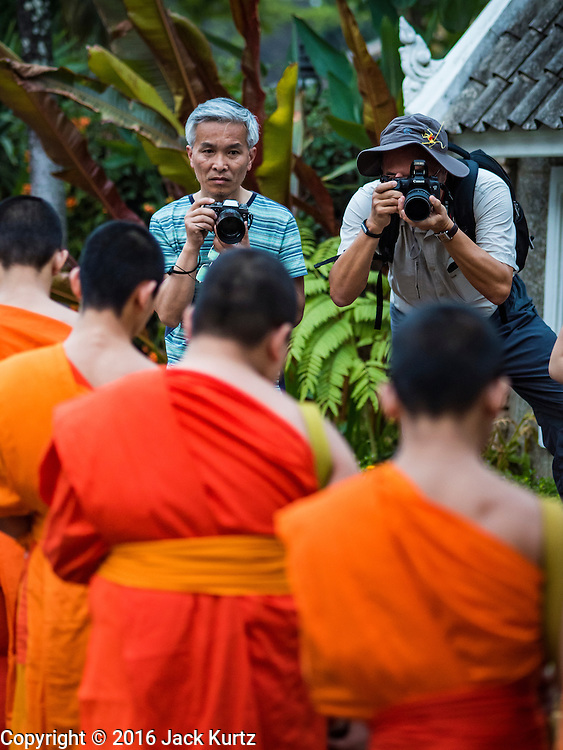 "12 MARCH 2016 - LUANG PRABANG, LAOS:  Tourists photograph Buddhist monks during the morning tak bat in Luang Prabang. Luang Prabang was named a UNESCO World Heritage Site in 1995. The move saved the city's colonial architecture but the explosion of mass tourism has taken a toll on the city's soul. According to one recent study, a small plot of land that sold for $8,000 three years ago now goes for $120,000. Many longtime residents are selling their homes and moving to small developments around the city. The old homes are then converted to guesthouses, restaurants and spas. The city is famous for the morning ""tak bat,"" or monks' morning alms rounds. Every morning hundreds of Buddhist monks come out before dawn and walk in a silent procession through the city accepting alms from residents. Now, most of the people presenting alms to the monks are tourists, since so many Lao people have moved outside of the city center. About 50,000 people are thought to live in the Luang Prabang area, the city received more than 530,000 tourists in 2014.      PHOTO BY JACK KURTZ"