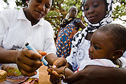 A health worker marks the finger of a child with ink during a national polio immunization exercise in the village of Gidan-Turu, northern Ghana on Thursday March 26, 2009.