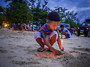 26 DECEMBER 2014 - PATONG, PHUKET, THAILAND: A Thai boy lights a candle at the beginning of the candle light service to memorialize the 2004 tsunami on Patong Beach in Patong, Phuket. Hundreds of people died in Patong and nearly 5400 people died on Thailand's Andaman during the 2004 Indian Ocean Tsunami that was spawned by an undersea earthquake off the Indonesian coast on Dec 26, 2004. In Thailand, many of the dead were tourists from Europe. More than 250,000 people were killed throughout the region, from Thailand to Kenya. There are memorial services across the Thai Andaman coast this weekend.    PHOTO BY JACK KURTZ