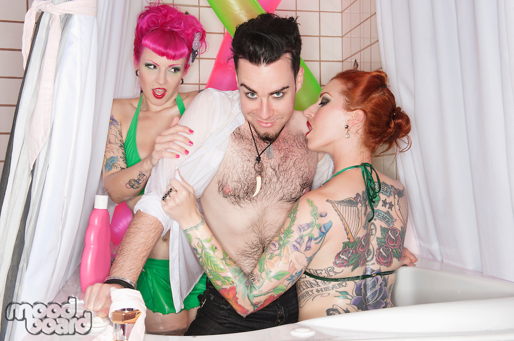 Erotic tattooed women seducing man in the bathtub