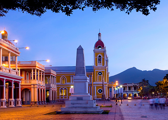 The neoclassical Cathedral of Granada rises above the Spanish colonial homes on Independence Plaza in Granada, Nicaragua.  The Mombacho Volcano can be seen<br />