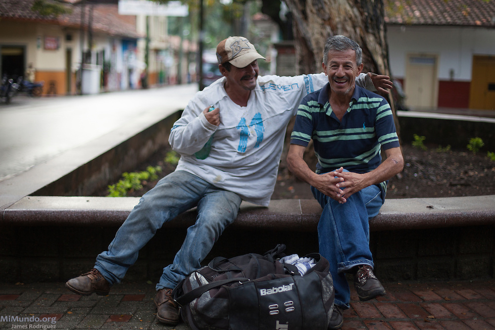 "Albeiro (left) and Javier (right) drink liquor in Ciudad Bolivar's central park at 7:15 AM. Javier states: ""I am here because unfortunately my family does not approve nor understand that I like to have a few drinks now and then."" Ciudad Bolivar, Antioquia, Colombia. September 26, 2013."