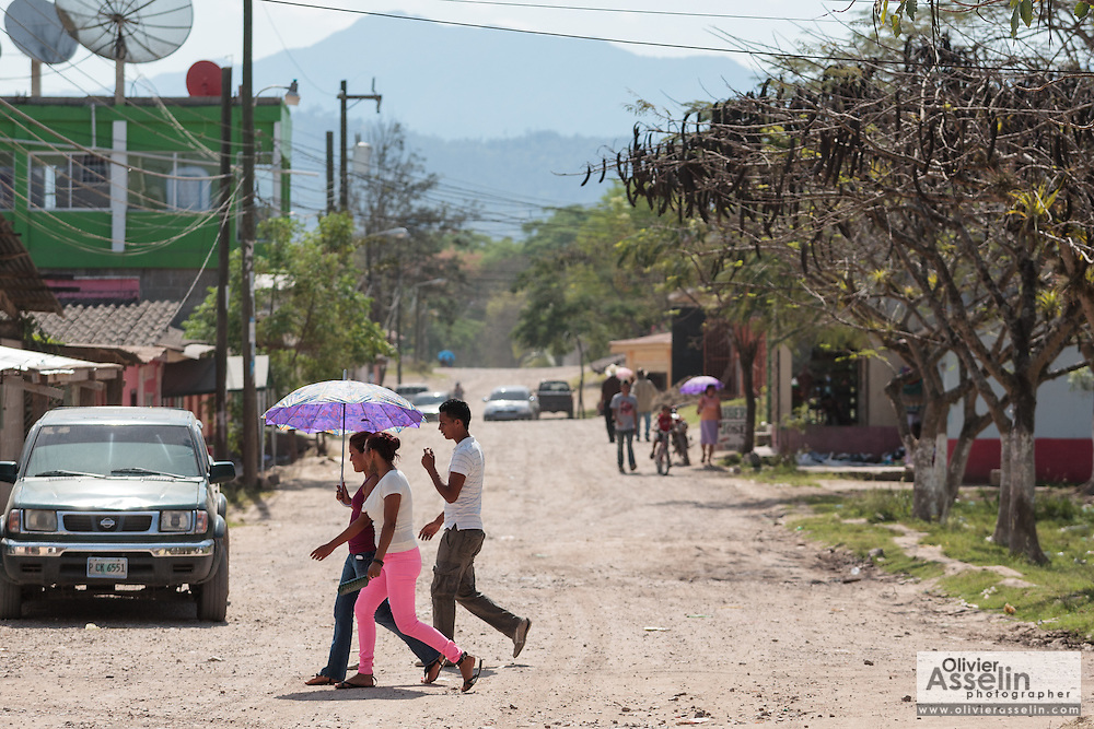 People walk across a street in the town of San Esteban, Honduras on Wednesday April 24, 2013.