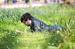 © Licensed to London News Pictures. 20/04/2016. London, UK. A man reading during warm weather in St James' park, central London. The MET Office predict highs of 13 degrees celsius. Photo credit : Tom Nicholson/LNP