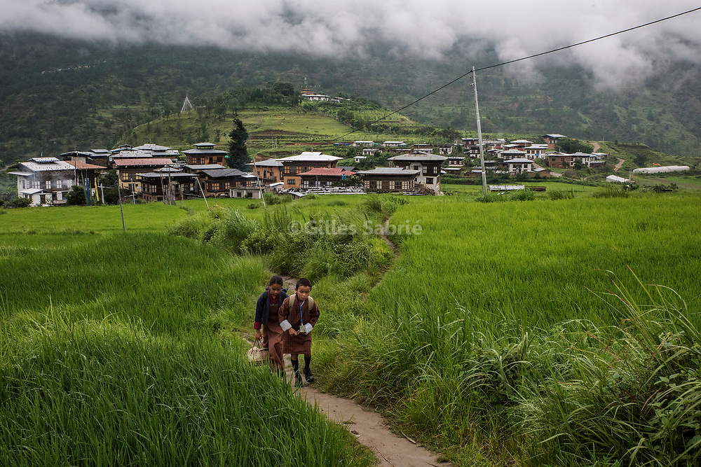 For a story by Steven Lee Myers, Bhutan<br /> Lobesa, Bhutan, August 2nd, 2017<br /> Children on their way to school in Lobesa village where the tradition of painting phalluses on the wall is particularly strong and brings scores of tourists. On the hill can be seen Chimi Lhakhang monastery, built on the site where it is said that Lama Drukpa Kunley  popularly known as the &ldquo;Divine Madman&quot;  subdued a demon with his &ldquo;magic thunderbolt of wisdom&rdquo;. <br /> Gilles Sabri&eacute; pour The New York Times