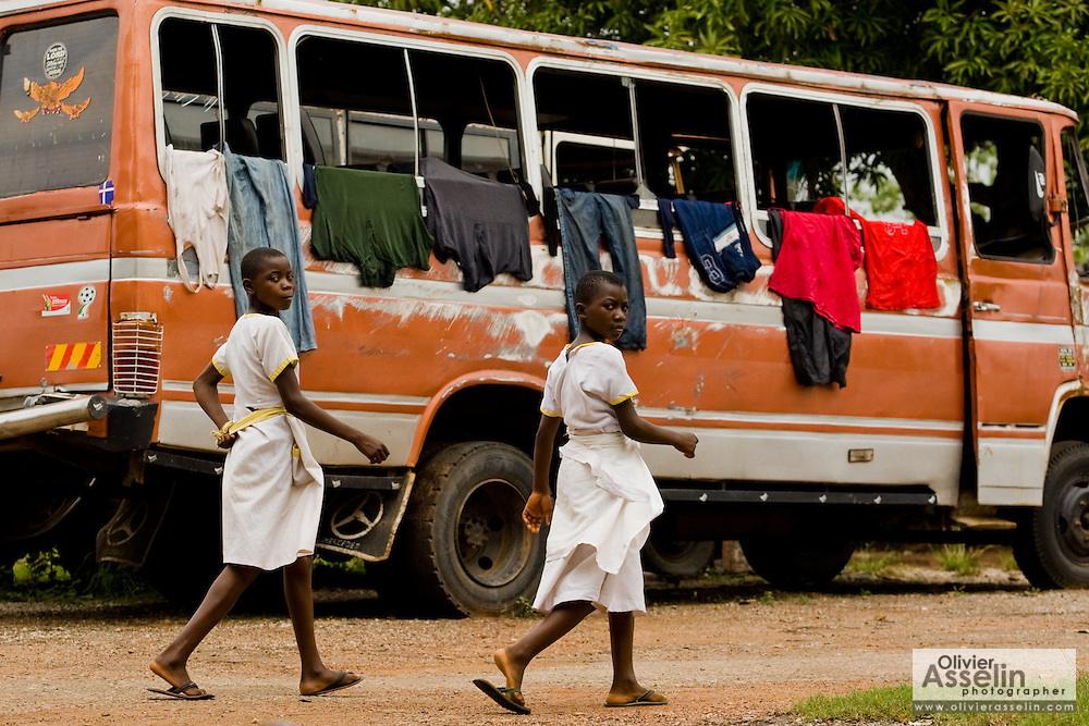 Girls in school uniforms walk past an old bus used to hang clothes in Kpong, Ghana on Wednesday June 17, 2009.