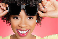 Portrait of a cheerful African American woman holding sunglasses over colored background
