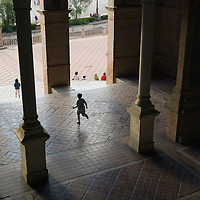 A boy running out of one of the buildings at the Plaza de España, Sevilla, Andalucia, Spain.