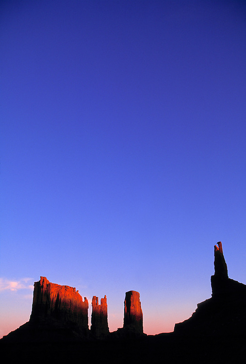 Sunrise shows its colors on the tops of the buttes in Monument Valley, Utah.