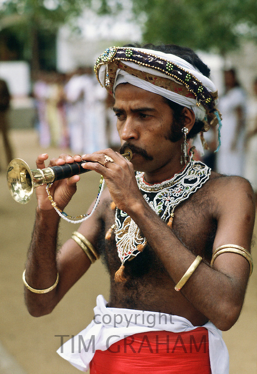 Man wearing  traditional Sri Lankan Costume and playing a trumpet, Sri Lanka. RESERVED USE - NOT FOR DOWNLOAD -  FOR USE CONTACT TIM GRAHAM