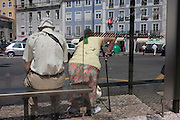 Elderly lady struggles to her feet with the use of a walking stick, in Lisbon, Portugal.