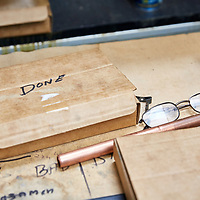 A photograph of a pair of glasses on a work bench in a british manufactuing facility