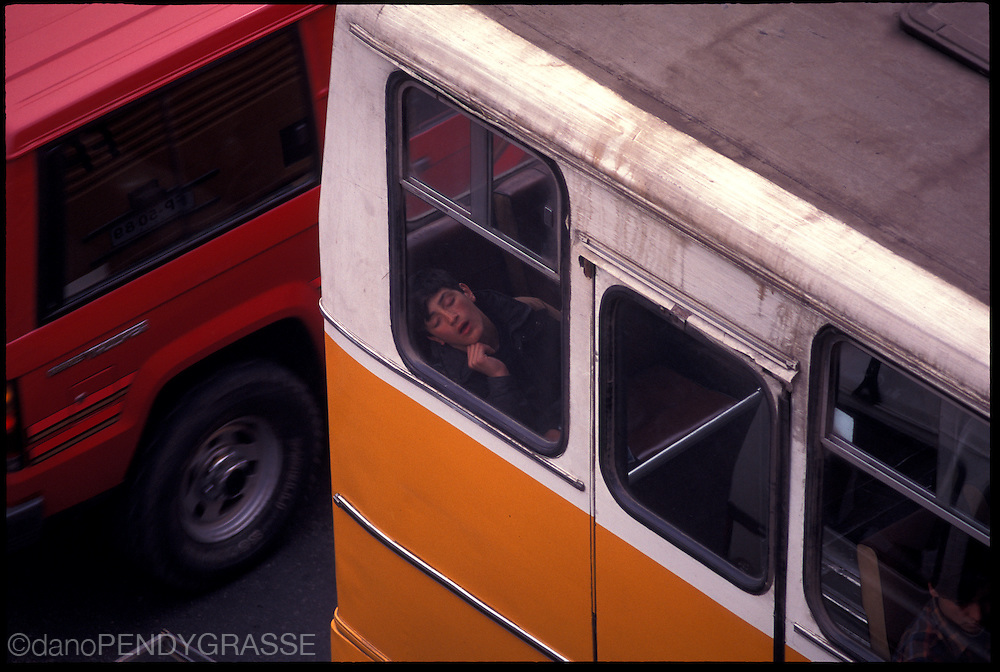 A boy sleeps on a public transit bus in Santiago, Chile.