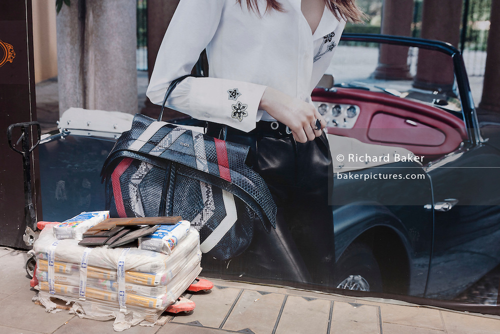 Advertising image juxtaposed with bags cement building materials on the ground in Bond Street, central London.