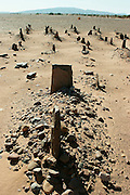 Berber cemetery in the Sahara, Morocco.  Recent grave, with headstone and rockpile, in the foreground; others beyond receding into the distant desert sand.