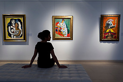 © Licensed to London News Pictures. 04/04/2013. London, UK. A Christie's employee sits in front of paintings including Andre Derain's 1905 portrait of the wife of Henri Matisse entitled 'Madame Matisse au kimono' (est. US$15,000,000-20,000,000) (C); Fernand Leger's 'Les deux figures' (1929, est. US$3,000,000-5,000,000) (L); and Pablo Picasso's 'Buste d'homme a la pipe' (1969, est US$900,000-1,200,000) at an auction press preview in St James, London, today (04/04/2013). The sale, consisting of Impressionist & Modern Art, is set to take place  on the 8th of May in Christie's New York premises.  Photo credit: Matt Cetti-Roberts/LNP