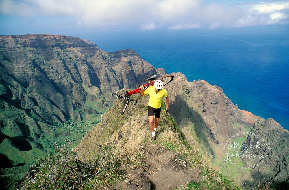 Hawaii, Kauai, Na Pali, Awaawapuhi, mountain biker carrying bike on razor edged ridge