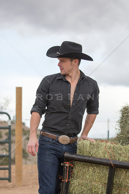 hot cowboy by a trailer with hay bales