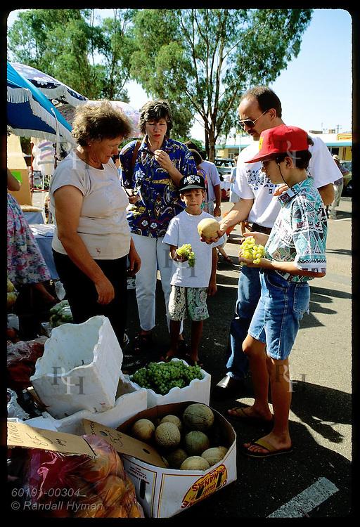 Zel Bodulovic and family, Yugoslavian immigrants, buy fruit at outdoor market; Wagga Wagga, NSW Australia