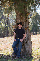 cowboy leaning against a tree