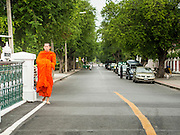 "21 JULY 2013 - BANGKOK, THAILAND:   A Buddhist monk walks along a street near Wat Benchamabophit on the first day of Vassa, the three-month annual retreat observed by Theravada monks and nuns. On the first day of Vassa (or Buddhist Lent) many Buddhists visit their temples to ""make merit."" During Vassa, monks and nuns remain inside monasteries and temple grounds, devoting their time to intensive meditation and study. Laypeople support the monastic sangha by bringing food, candles and other offerings to temples. Laypeople also often observe Vassa by giving up something, such as smoking or eating meat. For this reason, westerners sometimes call Vassa the ""Buddhist Lent.""      PHOTO BY JACK KURTZ"