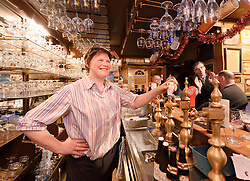 """BRUGES, BELGIUM - DEC-30-2010 - Daisy Claeys, the owner of 't Brugs Beertje, in Bruges, Belgium, serves her customers. The 't Brugs Beertje is considered by many beer aficionados as one of the best beer houses in Europe. """"If you are European, you cannot call yourself a well-travelled beer lover unless you have drunk at Daisy's,"""" writes British beer journalist Tim Webb in his essential traveler's tome, The Good Beer Guide to Belgium. (Photo © Jock Fistick)"""
