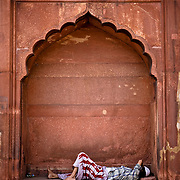 A man sleeps under the arch on the side of the Jamma Masjid.