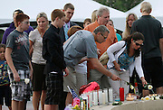 Family members of those killed in the Century theater shootings on July 20, 2012 leave flowers at a memorial after a prayer vigil for the victims in Aurora, Colorado July 22, 2012. REUTERS/Rick Wilking (UNITED STATES)