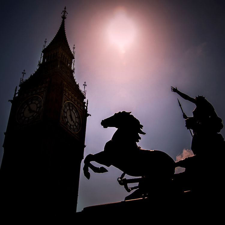 A statue of Queen Boadicea in silhuoette against an afternoon sun