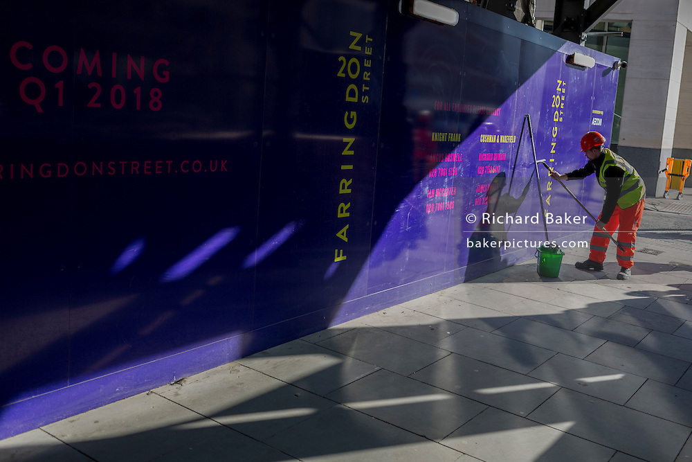 A contractor cleans construction hoarding on Farringdon Street, on 13th February 2017, in the City of London, United Kingdom.