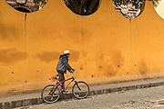 A Mexican cowboy pushes a bicycle through the streets of San Miguel de Allende, Mexico.