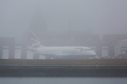 © Licensed to London News Pictures. 30/12/2016. LONDON, UK.  A British Airways plane sits on the runway at London City Airport, shrouded in fog this morning. London is experiencing more freezing and foggy weather this morning which has disrupted and delayed flights and travel.  Photo credit: Vickie Flores/LNP