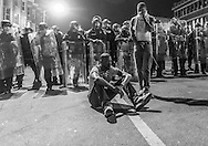 A protestor sits in the streets after violence erupted in Baltimore.